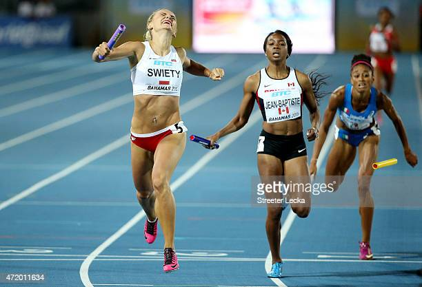 Justyna Swiety of Poland and Audrey JeanBaptiste of Canada cross the finish during round one of the women's 4 x 400 metres relay on day one of the...