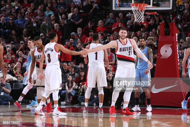 Jusuf Nurkic and CJ McCollum of the Portland Trail Blazers high five each other during the game against the Denver Nuggets on March 28 2017 at the...