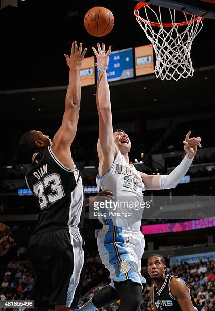 Jusuf Nurkic of the Denver Nuggets lays up a shot against the defense of Boris Diaw of the San Antonio Spurs at Pepsi Center on January 20 2015 in...