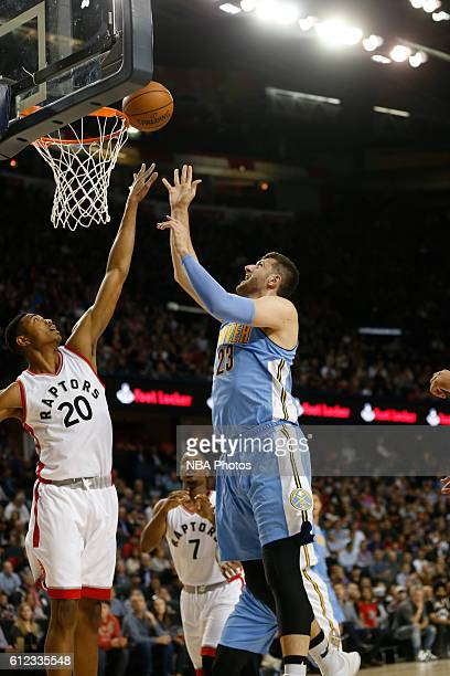 Jusuf Nurkic of the Denver Nuggets shoots the ball against Bruno Caboclo of the Toronto Raptors on October 3 2016 at the Scotiabank Saddledome in...