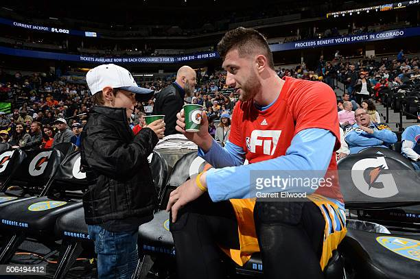 Jusuf Nurkic of the Denver Nuggets talks with a young fan before the game against the Detroit Pistons on January 23 2016 at the Pepsi Center in...