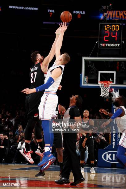 Jusuf Nurkic of the Portland Trail Blazers and Kristaps Porzingis of the New York Knicks reach for the jump ball to start the game between the two...