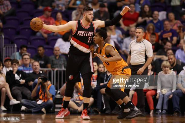 Jusuf Nurkic of the Portland Trail Blazers looks to pass guarded by Marquese Chriss of the Phoenix Suns during the first half of the NBA game at...