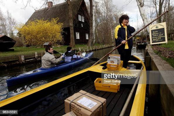 Jutta Pudenz an employee of German postal carrier Deutsche Post DHL stops to talk on a mobile phone while navigating her faltbottomed canoe through...