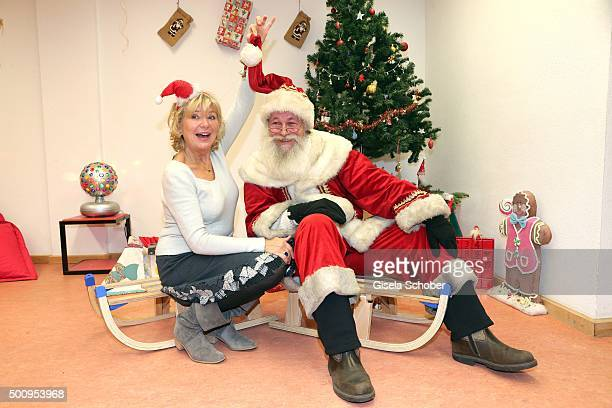 Jutta Speidel and Santa Claus pose during the Christmas party at Horizont eV on December 11 2015 in Munich Germany