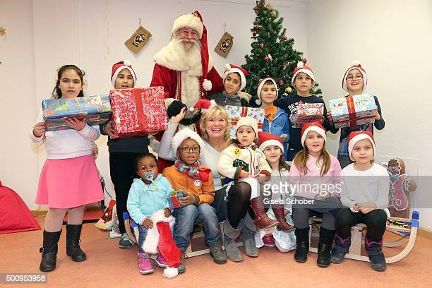 Jutta Speidel poses with a group of kids and a Santa Claus during the Christmas party at Horizont eV on December 11 2015 in Munich Germany