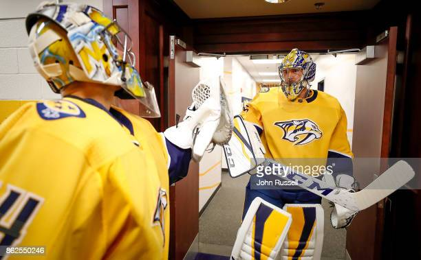 Juuse Saros glove taps Pekka Rinne of the Nashville Predators as they prepare to take the ice against the Colorado Avalanche during an NHL game at...