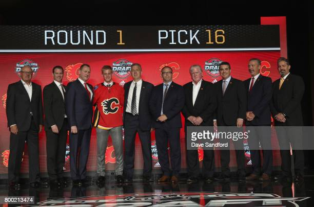 Juuso Valimaki 16th overall pick of the Calgary Flames poses onstage with the Flames draft team during Round One of the 2017 NHL Draft at United...