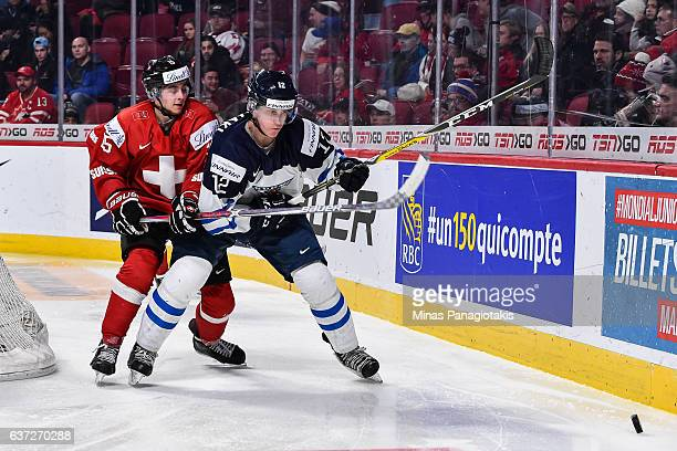 Juuso Valimaki of Team Finland and Nathan Marchon of Team Switzerland skate after the puck during the 2017 IIHF World Junior Championship preliminary...