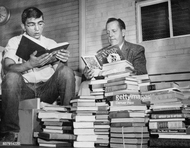 Juvenile Judge Philip B Gilliam and Dave Green of 2855 Oneida St scan some of the 1000 books collected by members of the Park Hill Area Teenagers...