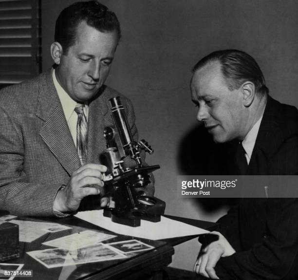 Juvenile Judge Philip B Gilliam and Dr Robert Werner director of a boys' reformatory at Rockenberg Germany examine a microscope which was donated to...
