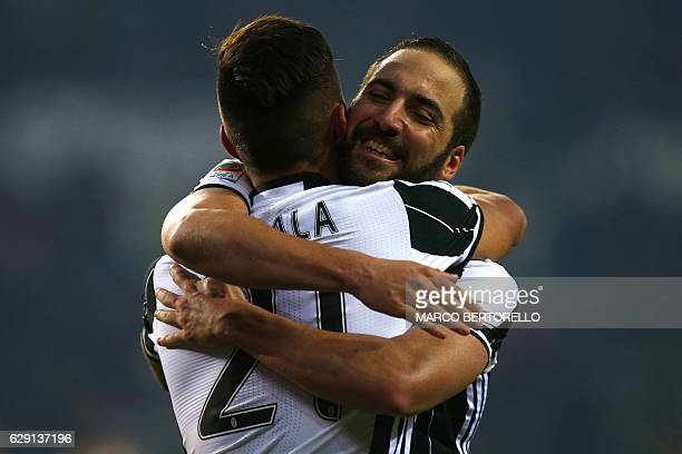 Juventus' Argentinan forward Gonzalo Higuain jubilates with Juventus' Argentinan forward Paulo Dybala at the end of the Italian Serie A football...
