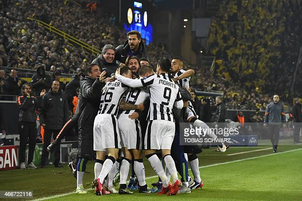 Juventus' Argentinian forward Carlos Tevez celebrates scoring with his teammates scores the 01 goal during the Round of 16 secondleg UEFA Champions...