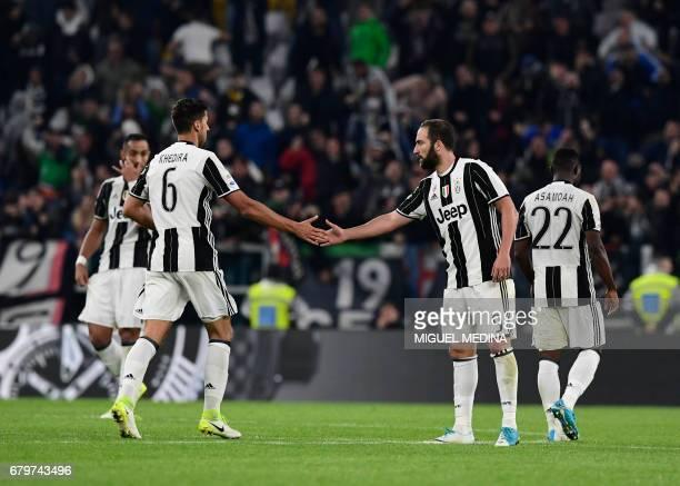 Juventus' Argentinian forward Gonzalo Gerardo Higuain is congratulated by Juventus' Germain midfielder Sami Khedira after scoring during the Italian...