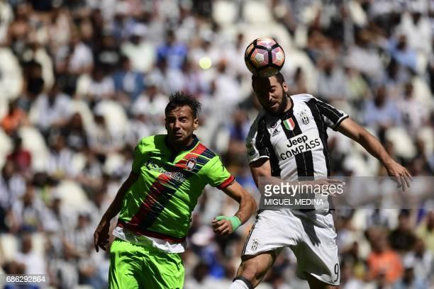 Juventus' Argentinian forward Gonzalo Gerardo Higuain vies with Crotone's Italian defender Gian Marco Ferrari during the Italian Serie A football...