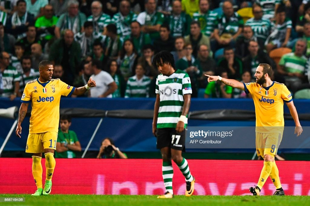 Juventus' Argentinian forward Gonzalo Higuain (R) celebrates a goal with teammate Juventus' Brazilian midfielder Douglas Costa (L) during the UEFA Champions League football match Sporting CP vs Juventus FC at the Jose Alvalade stadium in Lisbon on October 31, 2017. /