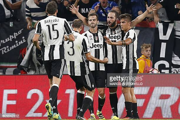 Juventus' Argentinian forward Gonzalo Higuain celebrates with teammates after scoring during the Italian Serie A football match between Juventus and...