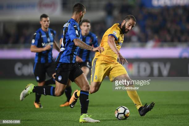 Juventus' Argentinian forward Gonzalo Higuain fights for the ball with Atalanta's Italian midfielder Leonardo Spinazzola during the Italian Serie A...