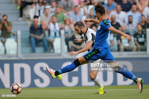 Juventus' Argentinian forward Gonzalo Higuain scores a goal during the Italian Serie A football match between Juventus and Sassuolo on September 10...