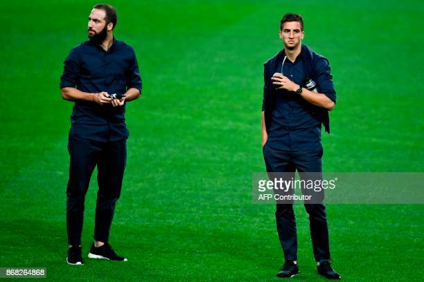 Juventus' Argentinian forward Gonzalo Higuain stands with Juventus' Uruguayan midfielder Rodrigo Bentancur as they walk on the pitch moments before a...