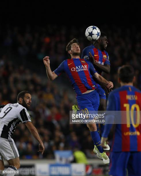 Juventus' Argentinian forward Gonzalo Higuain watches as Barcelona's midfielder Sergi Roberto and Barcelona's French defender Samuel Umtiti go for a...