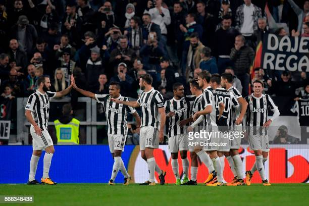 Juventus' Argentinian forward Paulo Dybala celebrates with teammates after scoring the first goal during the Italian Serie A football match Juventus...
