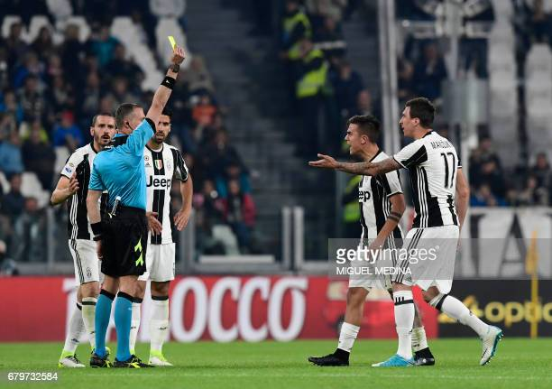Juventus' Argentinian forward Paulo Dybala receives a yellow card from referee Paolo Valeri during the Italian Serie A football match Juventus vs...