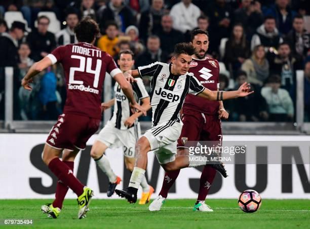 Juventus' Argentinian forward Paulo Dybala vies with Torino's Italian defender Cristian Molinaro and Torino's Italian defender Emiliano Moretti...