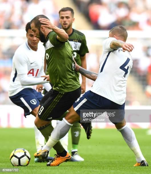 Juventus' Argentinian striker Gonzalo Higuain takes the ball past Tottenham Hotspur's Belgian defender Toby Alderweireld and Tottenham Hotspur's...
