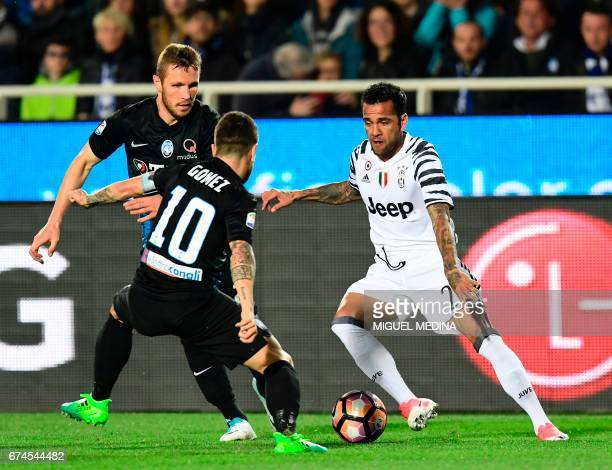 Juventus' Brazilian defender Daniel Alvez da Silva vies with Atalanta's Slovanian midfielder Jasmin Kurtic and Atalanta's Argentinian midfielder...