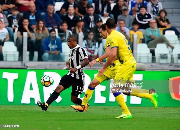 Juventu's Brazilian forward Douglas Costa de Souza vies with Chievo's players during the Italian Serie A football match Juventus vs Chievo at the...