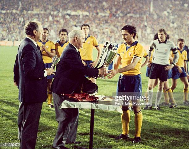 Juventus captain Gaetano Scirea receives the trophy from UEFA President Jacques Georges after their 20 victory over FC Porto in the European Cup...