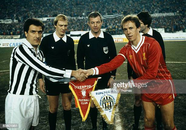 Juventus captain Gaetano Scirea shakes hands with Liverpool's Phil Neal watched by the referee and linesmen prior to the UEFA Super Cup Final at the...