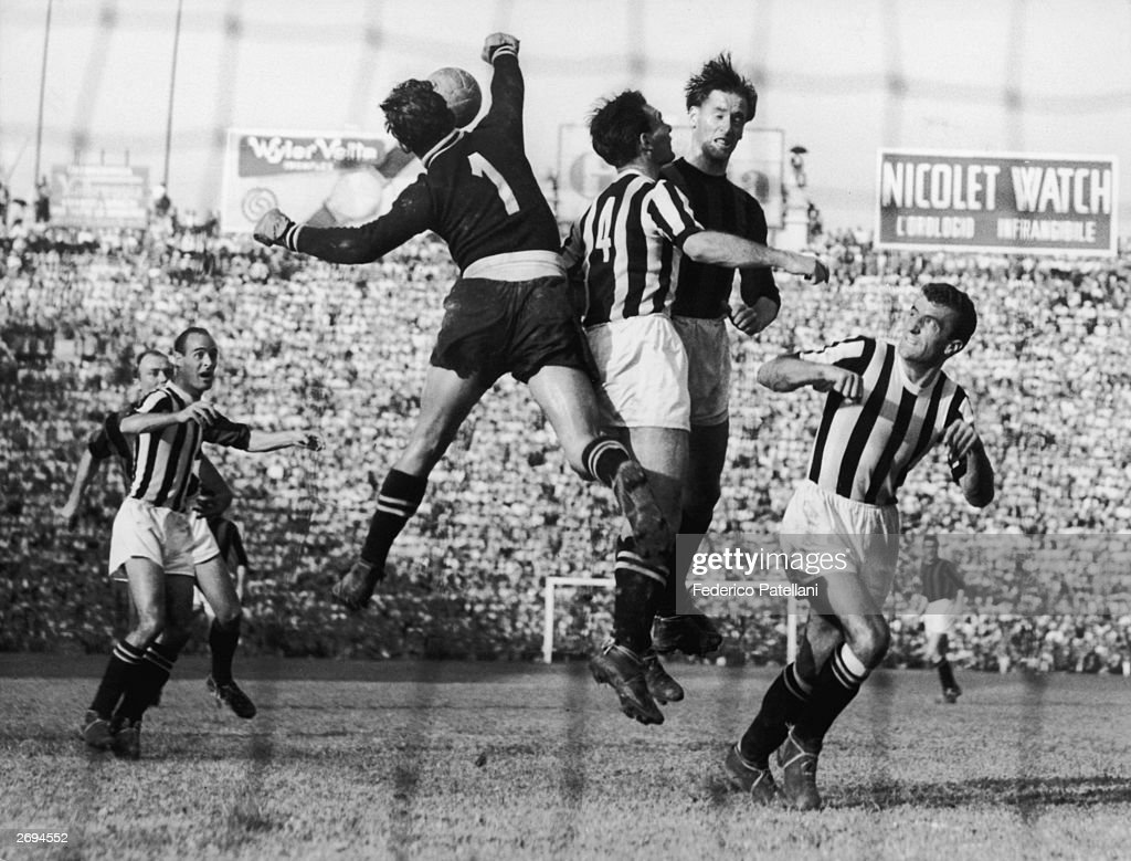 Juventus centre half Carlo Parola and his teammate Piccinina watching as a group of players challenge for the ball