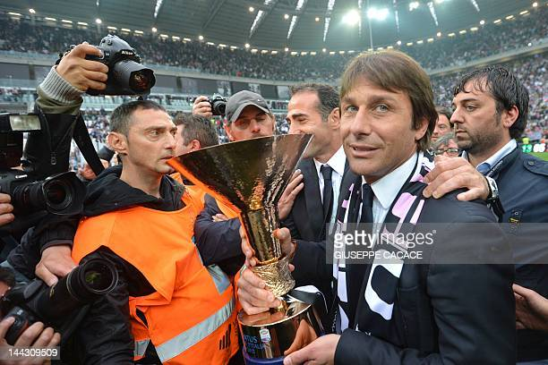 Juventus' coach Antonio Conte holds the Italian Serie A football trophy the Scudetto during a ceremony after the team's match against Atalanta on May...