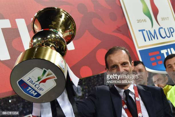 Juventus' coach from Italy Massimiliano Allegri holds the trophy after winning the Italian Tim Cup final on May 17 2017 at the Olympic stadium in...