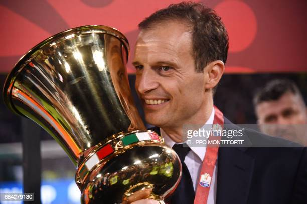 Juventus' coach from Italy Massimiliano Allegri poses with the trophy after winning the Italian Tim Cup final on May 17 2017 at the Olympic stadium...