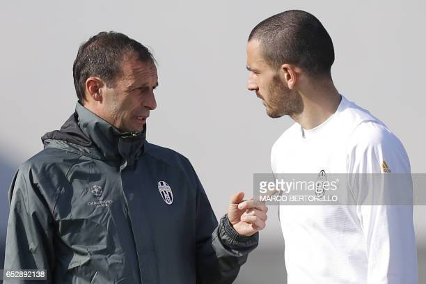Juventus' coach Massimiliano Allegri chats with Juventus' defender Leonardo Bonucci during a training session on the eve of the UEFA Champions League...