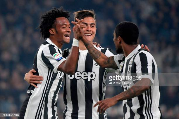 Juventus' Colombian forward Juan Cuadrado celebrates with Juventus' Argentinian forward Paulo Dybala and Juventu's Brazilian forward Douglas Costa de...