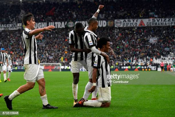 Juventus' Colombian forward Juan Cuadrado celebrates with teammates after scoring during the Italian Serie A football match Juventus vs Benevento at...