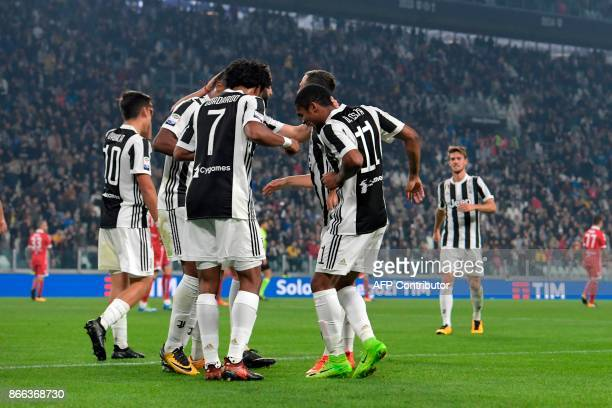 Juventus' Colombian forward Juan Cuadrado dances with teammates after scoring during the Italian Serie A football match Juventus vs Spal at the...
