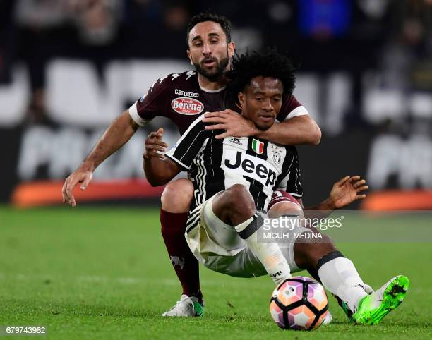 Juventus' Colombian forward Juan Cuadrado is tackled by Torino's Italian defender Cristian Molinaro during the Italian Serie A football match...