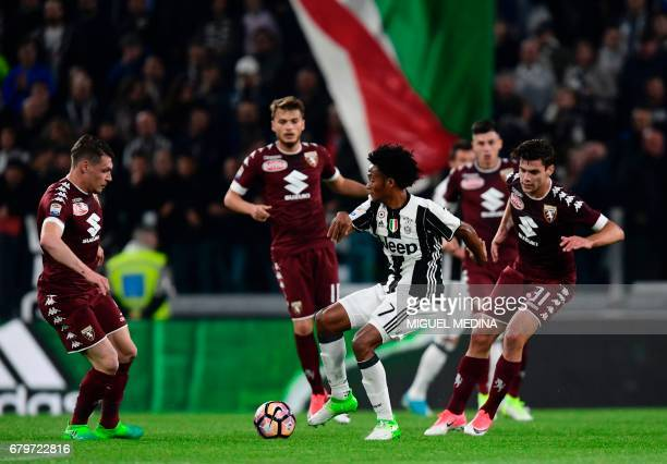 Juventus' Colombian forward Juan Cuadrado vies with Torino players during the Italian Serie A football match Juventus vs Torino FC at the Juventus...
