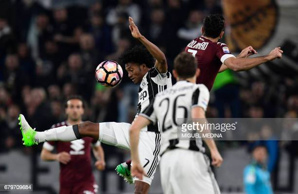 Juventus' Colombian forward Juan Cuadrado vies with Torino's Italian defender Cristian Molinaro during the Italian Serie A football match Juventus vs...