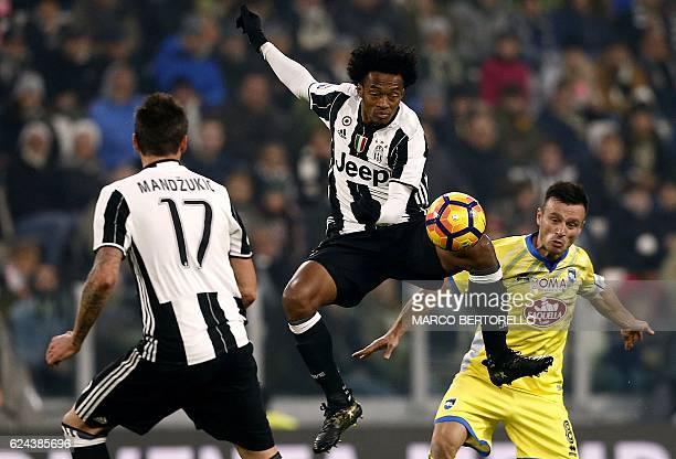 Juventus' Colombian midfielder Juan Cuadrado challenges Pescara's Albanian midfielder Ledian Memushaj during the Italian Serie A football match...