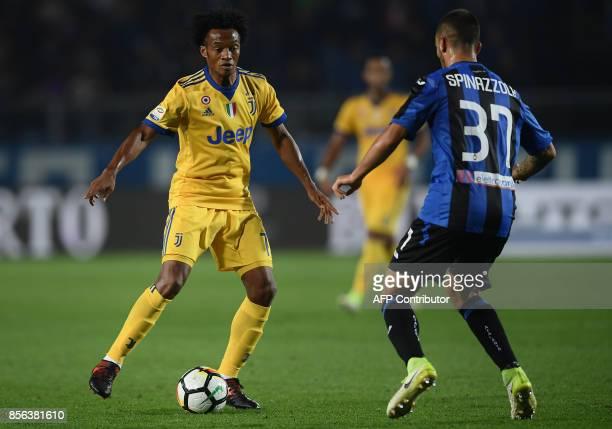 Juventus' Colombian midfielder Juan Cuadrado fights for the ball with Atalanta's Italian midfielder Leonardo Spinazzola during the Italian Serie A...