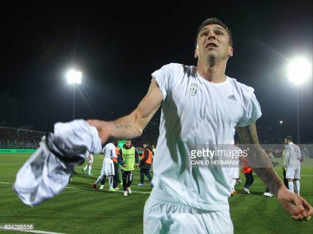 Juventus' Croatian forward Mario Mandzukic gives his jersey to supporters at the end of the Italian Serie A football match between FC Crotone and...