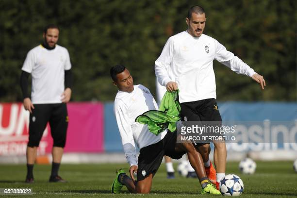 Juventus' defender Alex Sandro from Brazil and Juventus' defender Leonardo Bonucci take part in a training session on the eve of the UEFA Champions...