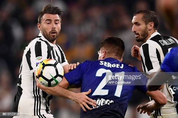 Juventus' defender Andrea Barzagli fights for the ball with Lazio's midfielder Sergej MilinkovicSavic from Serbia and Juventus' defender Giorgio...