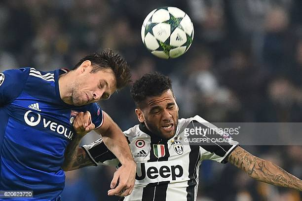 Juventus' defender Daniel Alves fights for the ball with Lyon's Polski defender Maciej Rybus during the UEFA Champions League football match Juventus...